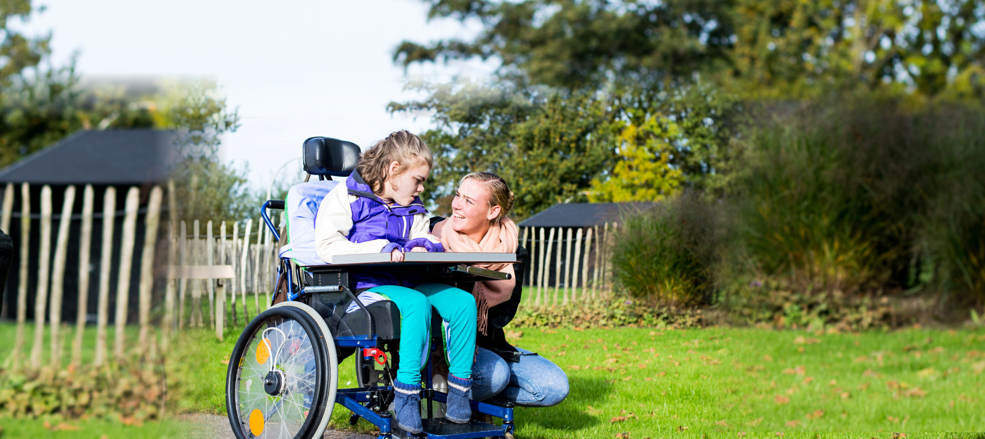 woman and girl with disability smiling