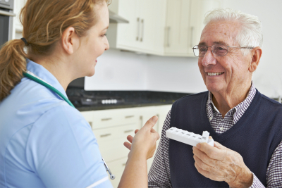 nurse advising senior man on medication
